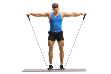 Full length portrait of a muscular guy exercising with a resistance band isolated on white background