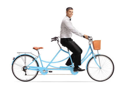 Full length profile shot of a smiling groom riding a tandem bicycle alone isolated on white background