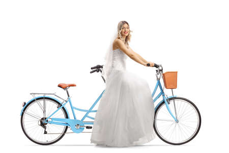 Full length shot of a beautiful bride riding a tandem bicycle and smiling at the camera isolated on white background