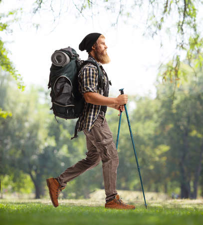 Full length profile shot of a young bearded hiker with a backpack and hiking poles walking in nature Stock fotó