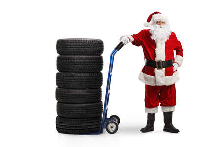 Full length portrait of a Santa Claus auto mechanic with car tires on a hand truck isolated on white background