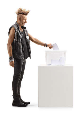 Full length profile shot of a punk with a mohawk putting a vote in an election box isolated on white background