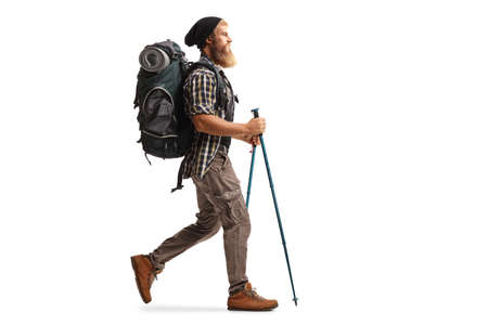 Full length profile shot of a bearded man with a backpack and hiking poles walking isolated on white background