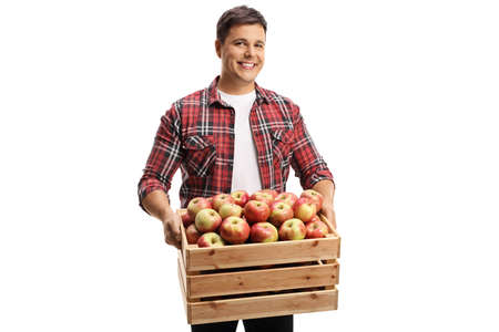 Young man smiling and carrying a crate full of fresh apples isolated on white background