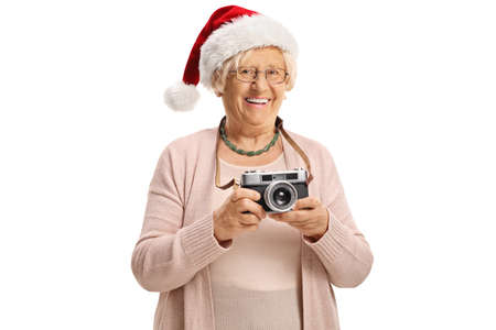 Elderly lady wearing a santa claus hat and holding a vintage camera isolated on white background
