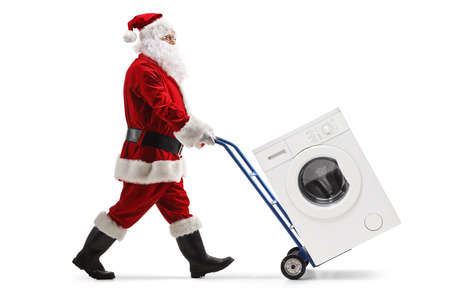 Full length portrait of a santa claus pushing a washing machine on a hand truck isolated on white background