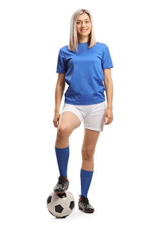 Full length portrait of a female football player with a soccer ball and smiling isolated on white background