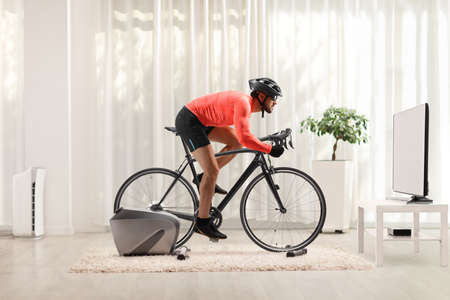 Young fit man cycling with stationary bicycle trainer at home in front of tv