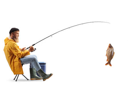 Full length profile shot of a young fisherman sitting on a chair and catching fish isolated on white background