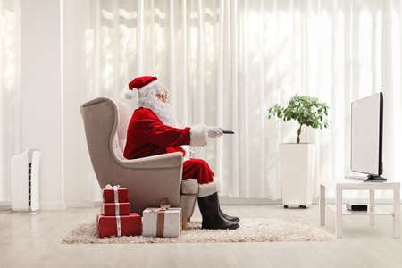 Full length profile shot of santa claus in armchair with a remote control in front of tv at home with presents on the floor