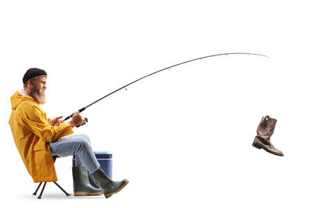 Bearded fisherman on a chair catching an old boot with a fishing rod isolated on white background