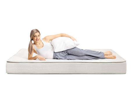 Young woman lying on a bed mattress in pajamas and holding a pillow isolated on white background Archivio Fotografico