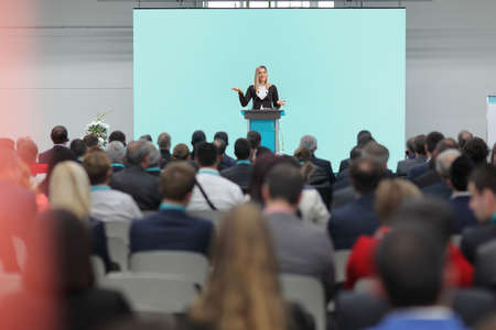 Businesswoman speaking on a pedestal on a conference in front of an audience