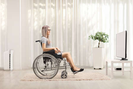 Profile shot of a young blond woman in a wheelchair watching tv