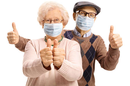 Elderly man and woman with protective face masks showing thumbs up isolated on white background