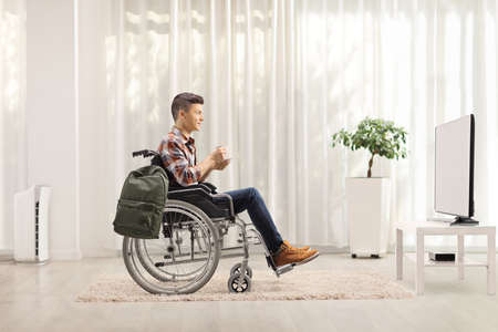 Full length profile shot of a young man in a wheelchair with a cup of tea watching tv