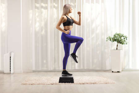 Full length profile shot of a young woman exercising step aerobic in a room 版權商用圖片