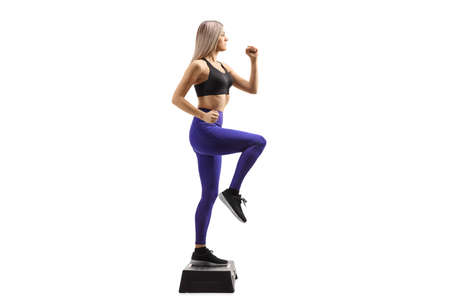 Full length profile shot of a woman exercising aerobic on a stepper isolated on white background