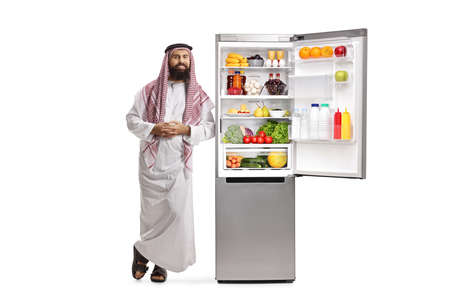 Full length portrait of a saudi arab man leaning on a fridge with food isolated on white background