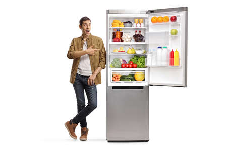 Full length portrait of a young man pointing at a fridge with food isolated on white background Stockfoto