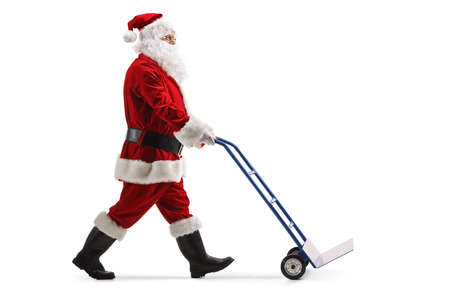 Full length profile shot of santa claus pushing an empty hand truck isolated on white background Stockfoto
