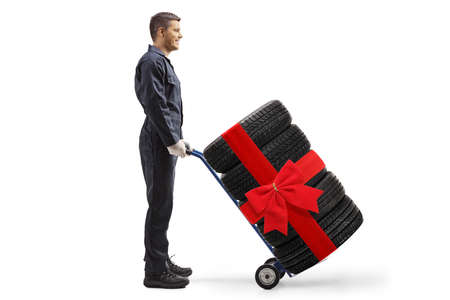 Full length profile shot of a mechanic worker pushing car tires with a red bow on a hand truck isolated on white background