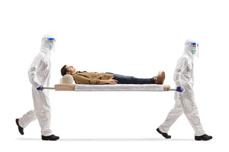 Health workers in hazmat suits carrying young male patient on a stretcher isolated on white background