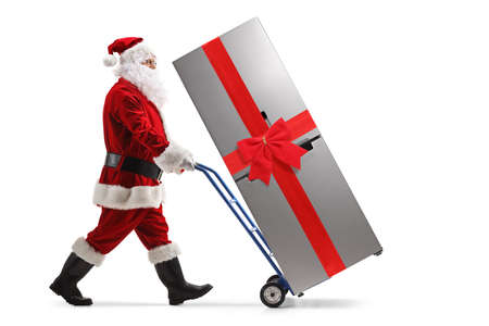 Full length portrait of santa claus pushing a fridge with a red bow on a hand truck isolated on white background