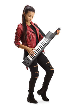 Cute young female in a leather jacket playing a keytar isolated on white background
