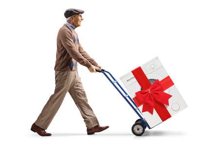 Elderly man pushing a washing machine with a red bow on a hand truck isolated on white background