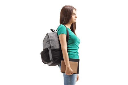 Serious female student carrying a backpack and holding books isolated on white background