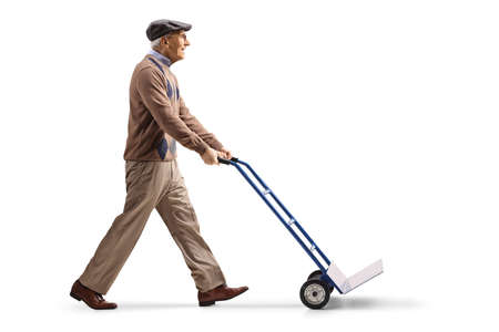 Full length profile shot of an elderly man pushing a hand truck isolated on white background
