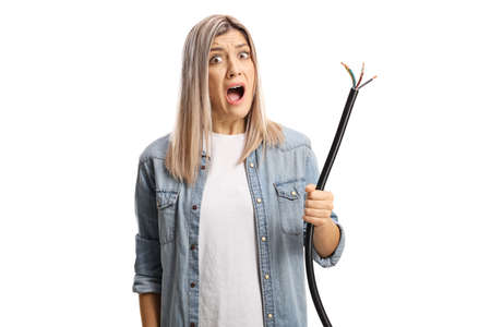 Angry displeased young woman holding a broken cable isolated on white background