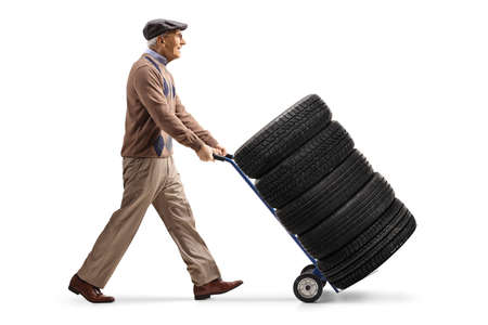 Full length profile shot of an elderly man pushing tires on a hand truck isolated on white background