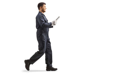 Full length profile shot of a young male worker in an overall uniform holding a clipboard and walking isolated on white background