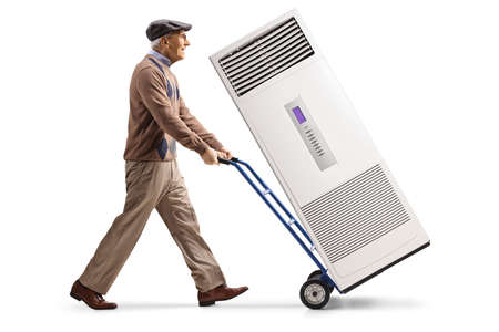 Elderly man walking and pushing an air conditioning unit on a hand truck isolated on white background Stockfoto
