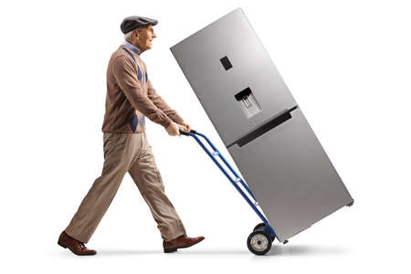Full length profile shot of an elderly man pushing a refrigerator on a hand truck isolated on white background