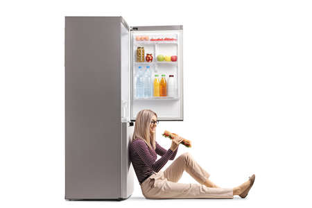 Young woman holding a sandwich and leaning on a fridge isolated on white background Stock Photo