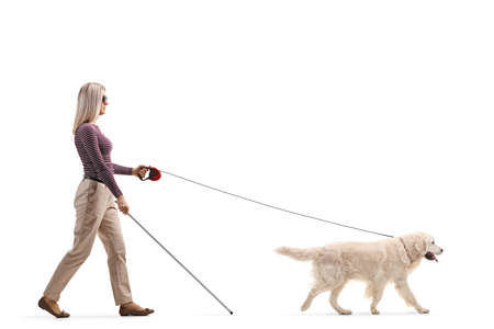 Full length profile shot of a young blind woman with a dog on a lead isolated on white background