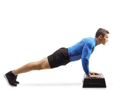 Muscular man exercising push-ups on a step aerobic platform isolated on white background Standard-Bild