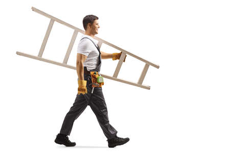 Full length profile shot of a repairman in uniform walking and carrying a white ladder isolated on white background