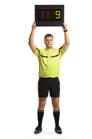 Full length portrait of football referee holding a substitute board isolated on white background