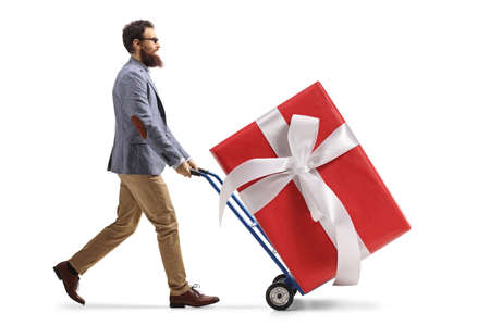 Bearded man pushing a hand truck with a big present isolated on white background