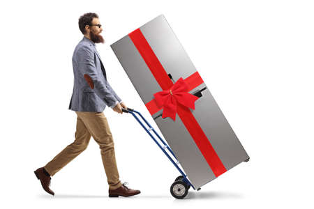 Bearded man pushing a hand truck with a fridge tied with a red ribbon isolated on white background
