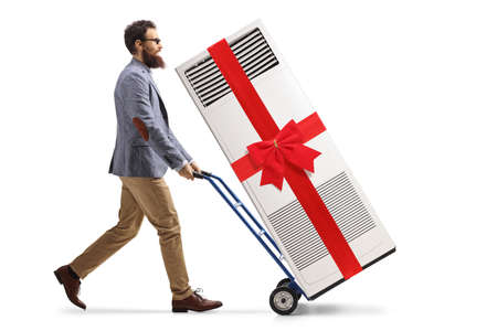 Full length profile shot of a bearded man pushing a hand truck with a portable air conditioner tied with a red ribbon isolated on white background