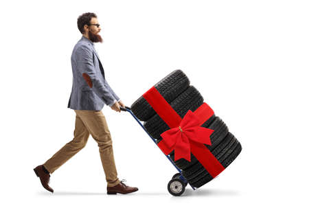 Full length profile shot of a bearded man pushing a hand truck with tires tied with a red ribbon bow isolated on white background
