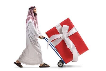 Saudi arab man pushing a hand truck with a big wrapped present box isolated on white background