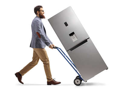 Full length profile shot of a bearded man walking and pushing a hand truck with a refrigerator isolated on white background