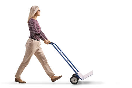 Full length profile shot of a young woman pushing an empty hand-truck isolated on white background