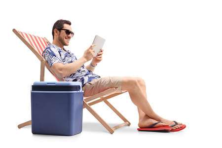 Young man sitting in a deck chair next to a cooling box and holding a digital tablet isolated on white background Banque d'images